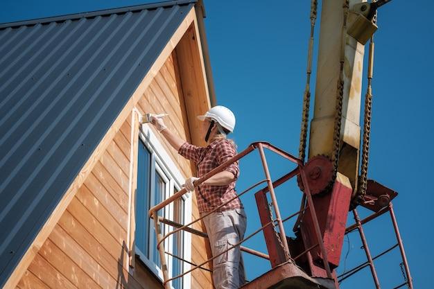 젊은 여자가 공중 플랫폼으로 꼭대기 층에 목조 주택의 창틀을 그립니다.