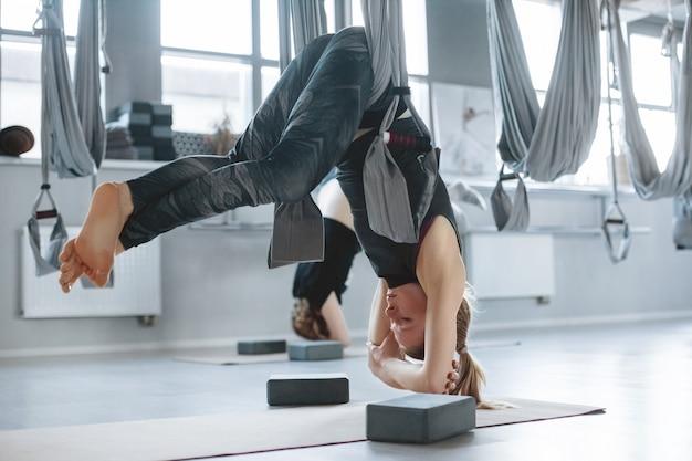 Молодая женщина выполняет воздушные упражнения йоги с гамаком в тренажерном зале