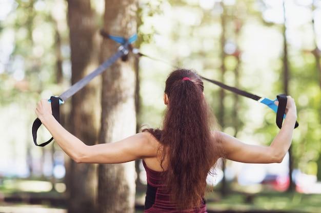 Молодая женщина выполняет упражнение для тренировки мышц спины на подвесном тренажере, прикрепленном к дереву в парке.