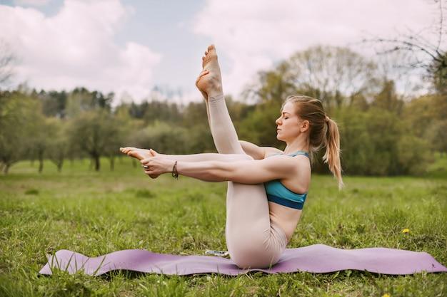 Молодая женщина выполняет асаны йоги на открытом воздухе в парке.