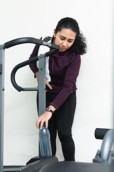 운동을 시작하기 전에 체육관의 러닝머신에 물 한 병을 놓는 젊은 여성