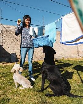 Молодая женщина играет с черной собакой и белой собакой, развешивая одежду на заднем дворе