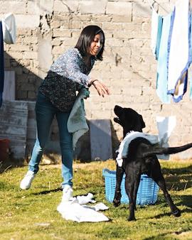 Молодая женщина играет с черной собакой, развешивая одежду на заднем дворе