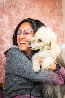 그녀의 침실에서 그녀의 작은 강아지와 함께 노는 젊은 여자