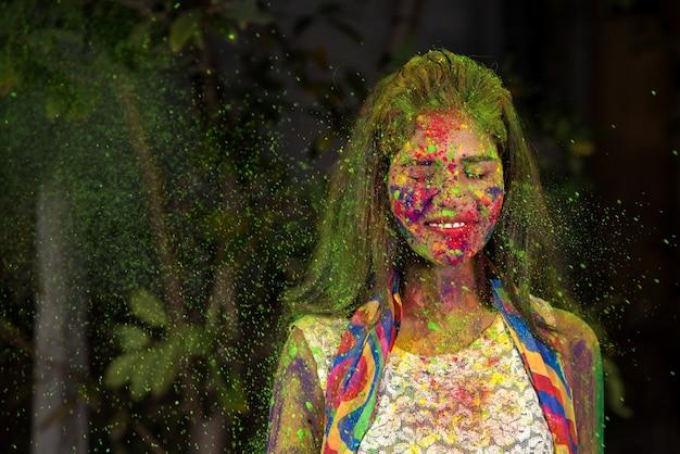 Молодая женщина играет с красками. концепция индийского фестиваля холи.