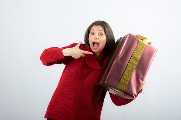 크리스마스 선물 상자를 가리키는 젊은 여자.