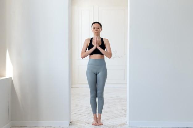 한 젊은 여성이 밝은 방의 아치에서 요가를 하고 기도하고 선을 이해합니다. 건강한 생활 방식, 명상 및 평온의 개념.