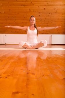 屋根裏部屋のスタジオでヨガを練習している若い女性。