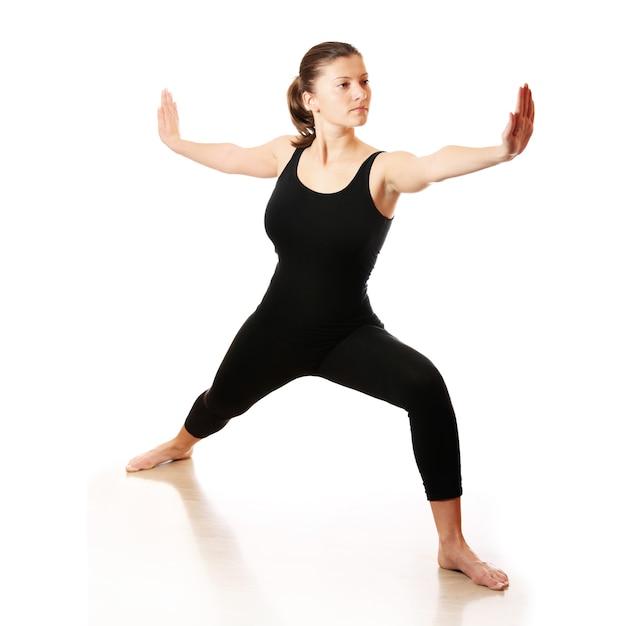 白い背景の上でヨガを練習している若い女性