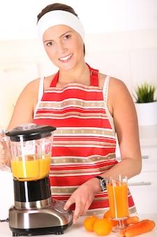 부엌에서 신선한 과일 주스를 준비하는 젊은 여자