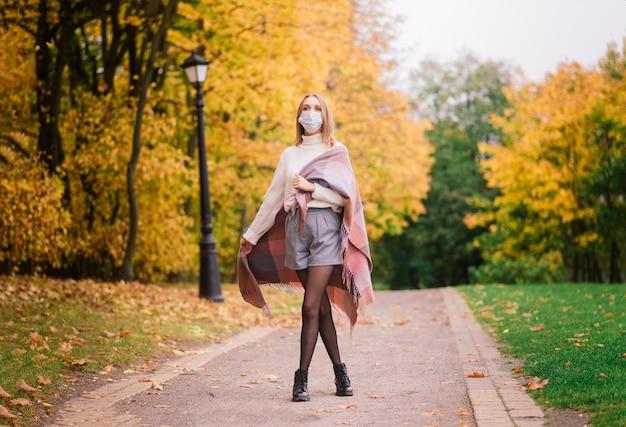 Молодая женщина защищает от вируса короны во время прогулки в парке. осенний фон.