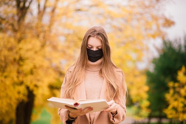 公園を歩いているときにコロナウイルスから保護する若い女性。秋の背景。