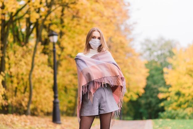 공원에서 걸을 때 코로나 바이러스로부터 보호하는 젊은 여성. 가을 배경.