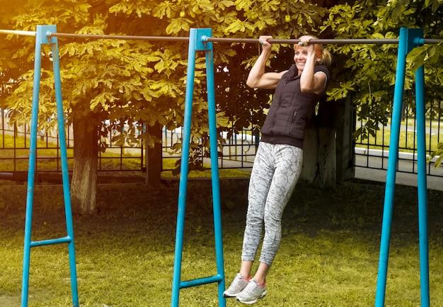 若い女性がクロスバーを引き上げる。フィットネス。健康的な生活様式。