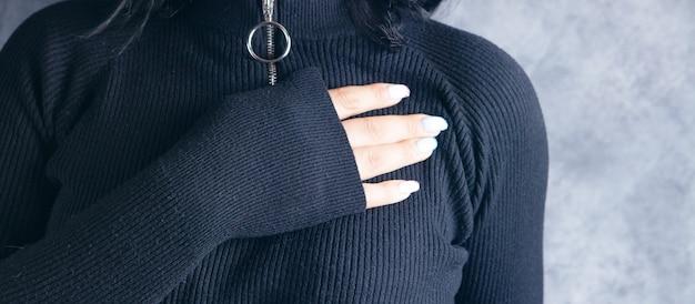 한 젊은 여성이 회색 배경의 가슴에 손을 얹었다