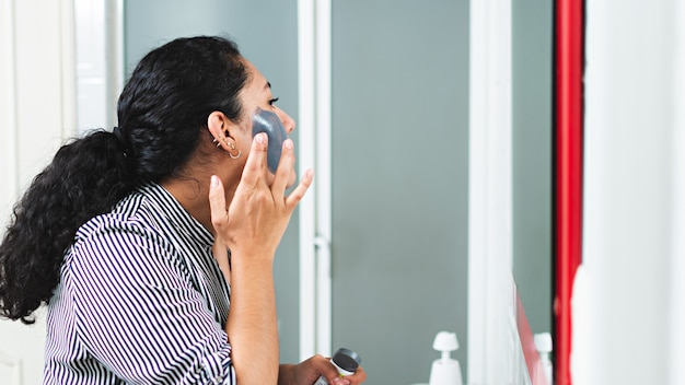 화장실 거울 앞에서 얼굴 마스크를 쓰고 있는 젊은 여성