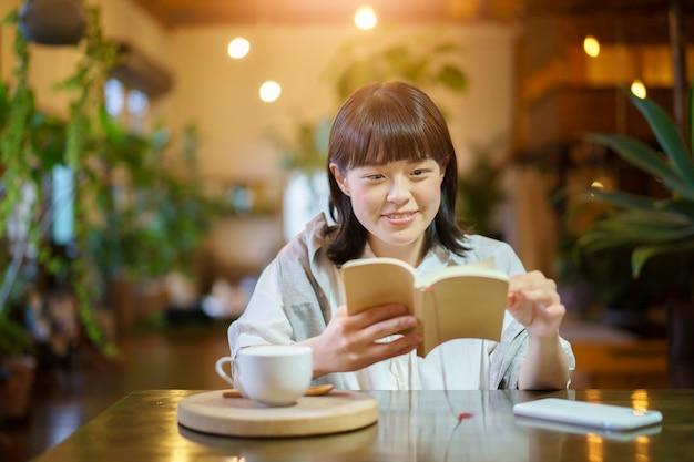 暖かい雰囲気の中で本を読んでいる若い女性 Premium写真