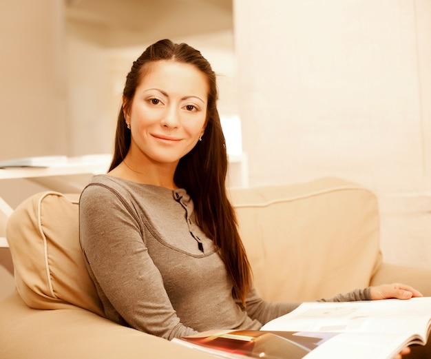 Молодая женщина читает журнал, сидя на диване