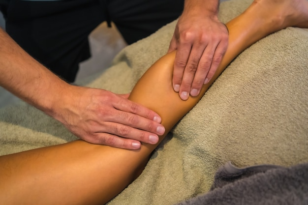 理学療法士から後ろ足マッサージを受けている若い女性。理学療法、オステオパシー