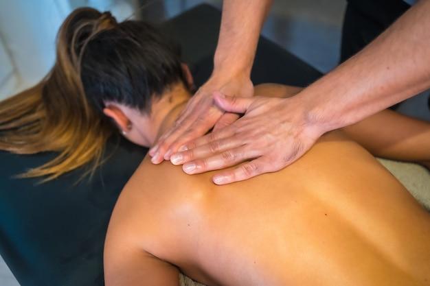理学療法士が手で背中のマッサージを受けている若い女性。