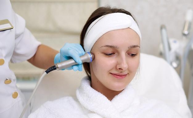 Молодая женщина получает омоложение лица. гидро-микродермабразионный пилинг для лица