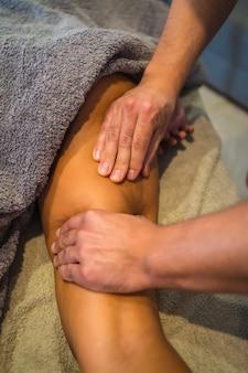 理学療法士から内肢マッサージを受けている若い女性。理学療法、オステオパシー