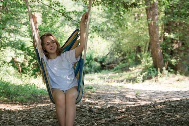 Молодая женщина отдыхает в гамаке в лесу.