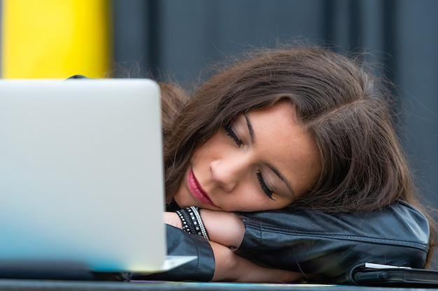 屋外のカフェテーブルで腕を組んで頭を支えながら目を閉じて仕事を休んでいる若い女性