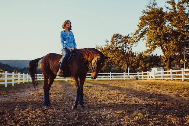Молодая женщина верхом на лошади смотрит на закат