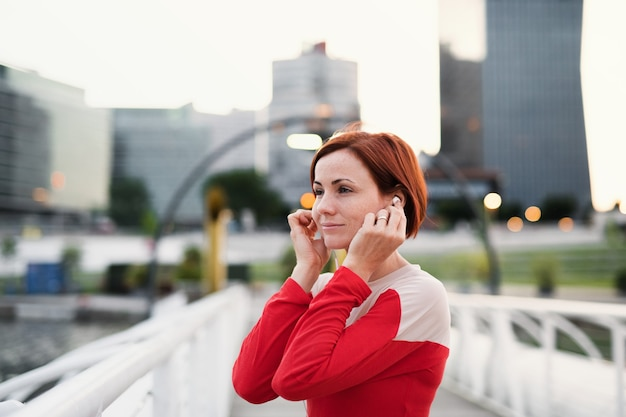 도시에서 이어폰을 끼고 다리에서 쉬고 있는 젊은 여성 주자.