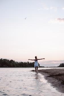 젊은 여성이 강둑에 하얀 여름 드레스를 입고 아름다운 금발의 해변을 따라 달리고 있습니다.