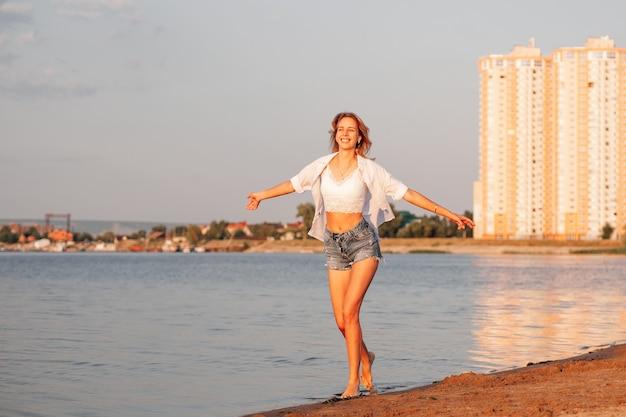 若い女性が白いシャツとデニムのショートパンツで幸せな笑顔のブロンドをビーチに沿って自由に走ります...