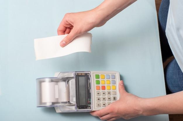 製品を購入した後、レジから小切手を引き裂く若い女性の手