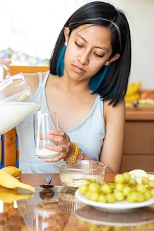 ガラスのコップにミルクを注いでテーブルに座っている若い女性