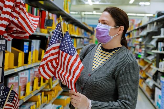 コロナウイルスcovid-19でマスクの下で顔にウイルスの流行中にスーパーマーケットで買い物をしている若い女性