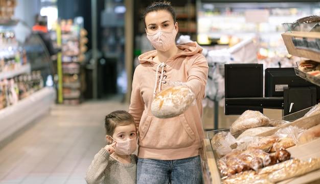 ウイルスの流行中にスーパーで買い物をする若い女性。顔にマスクをかぶっています。