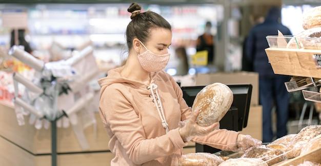 Молодая женщина делает покупки в супермаркете во время вирусной эпидемии.