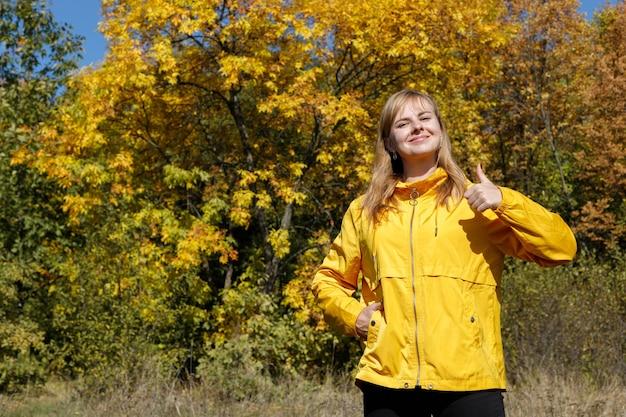 若い女性がクラスに秋の黄色い木を見せます。テキスト用の空き容量