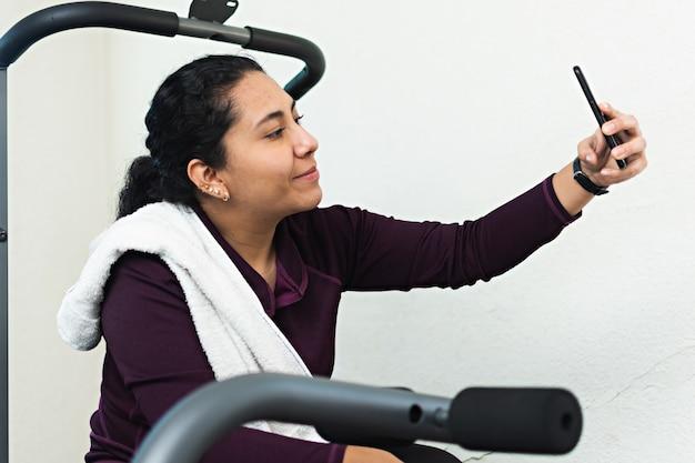 휴식 시간에 체육관에서 셀카를 찍고 있는 러닝머신에 앉아 있는 젊은 여성