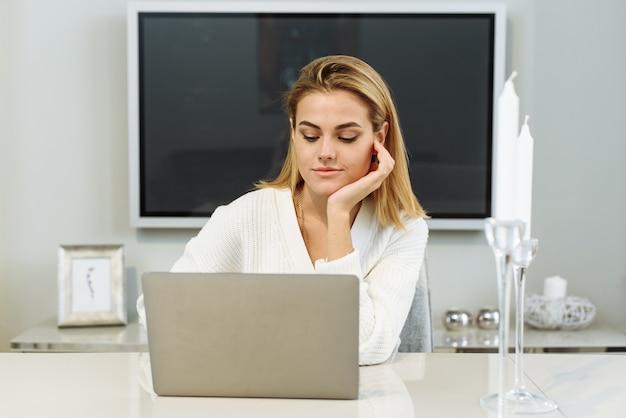 한 젊은 여성이 집에 있는 테이블에 앉아 노트북으로 일합니다. 사업가 프리랜서.