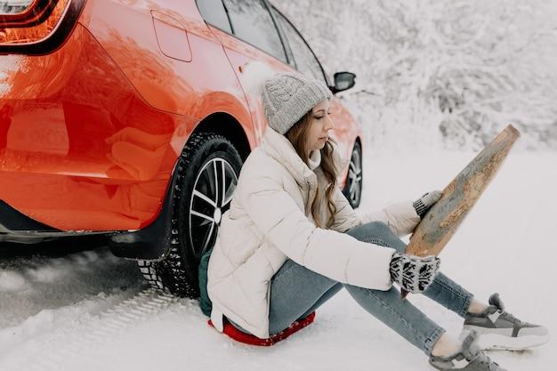 若い女性が赤い車のそばに座って、地図を手に持っています。旅行のコンセプト。