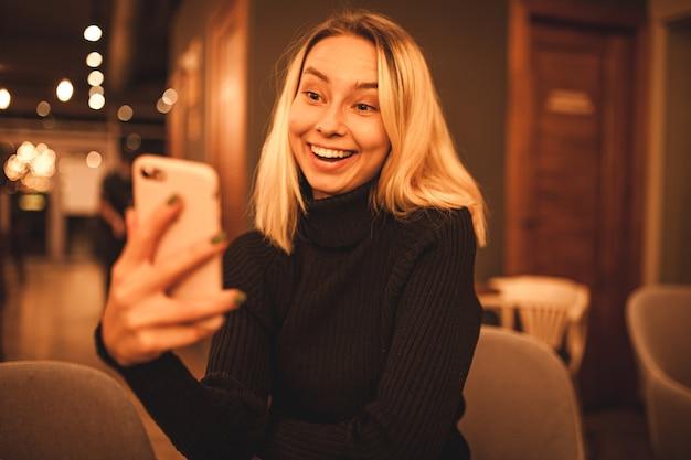 젊은 여자가 카페에 앉아 전화로 말한다 행복한 금발은 카페에서 쉬고있다 검은 스웨터에 여자의 초상화 사진