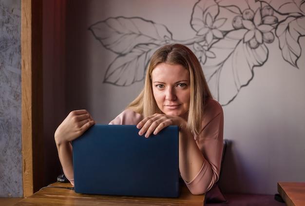 ノートパソコンを持ってカフェに座っている若い女性
