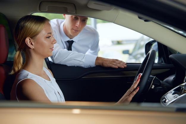 販売代理店が新車について話している間、若い女性が車の中に座っています