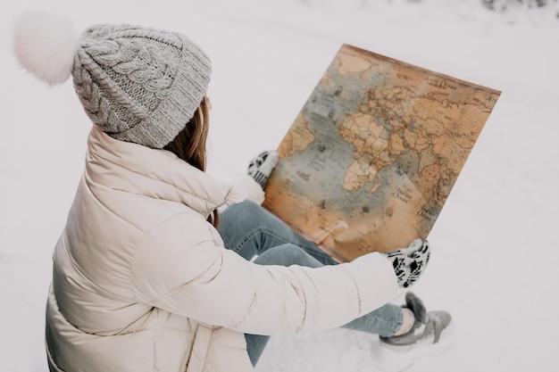 若い女性が雪の中に座って地図を手に持っています。旅行のコンセプト。