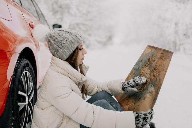 若い女性が赤い車の車輪で雪の中に座って、彼女の手で地図を持っています。旅行のコンセプト。