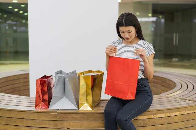 若い女性がショッピングセンターのベンチに座っています。赤い紙袋を入れます。中を見ます。