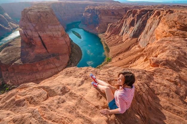 한 젊은 여성이 애리조나 페이지의 호스슈 벤드가 내려다보이는 절벽 가장자리에 앉아 있습니다.