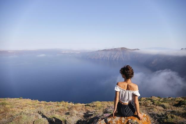 Молодая женщина сидит на краю горы и наслаждается видом.