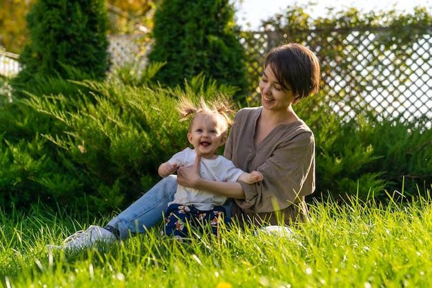 Молодая женщина сидит на лужайке перед домом и держит на руках годовалую дочь.